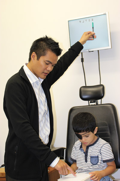 Optometrist testing visual acuity of a young child